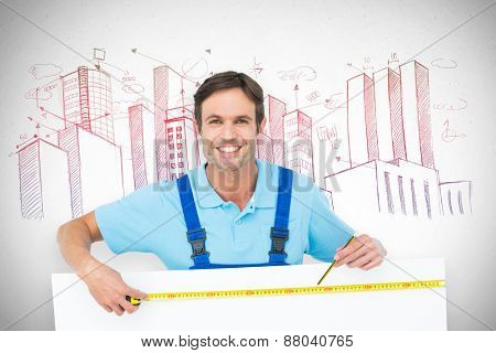Happy carpenter measuring blank bill board against grey