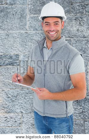 Portrait of smiling supervisor writing on clipboard against grey