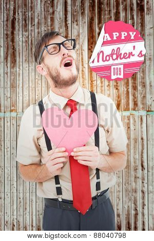 Geeky hipster crying and holding heart card against wooden planks