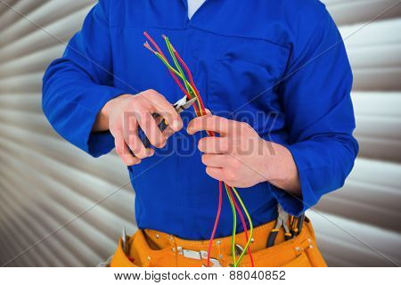 Electrician cutting wire with pliers against grey shutters
