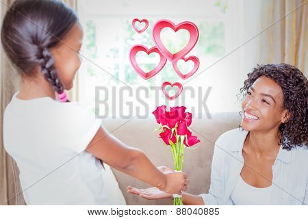 Pink hearts against pretty mother sitting on the couch with her daughter offering roses