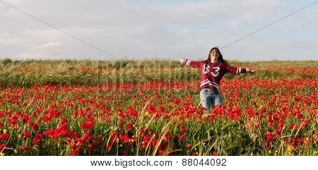 Happy Teenage Girl Jumping In A Red Field Of Poppy Flowers