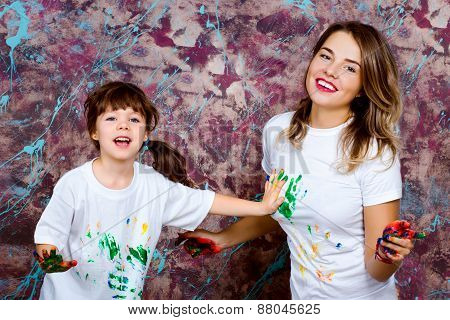Mother Together With A Daughter Is Shown With Palms Soiled With A Paint Of Different Colors, Smile.