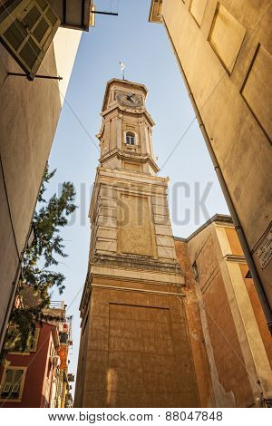 View of the clock tower of Saint Francois in Nice, France, from narrow street in old Nice.