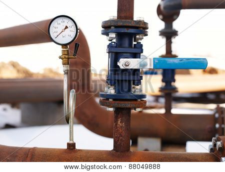 blue valve and manometer on rusty pipe