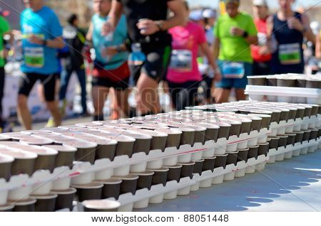 Marathon running race, runners on road, volunteer giving water and isotonic drinks on refreshment