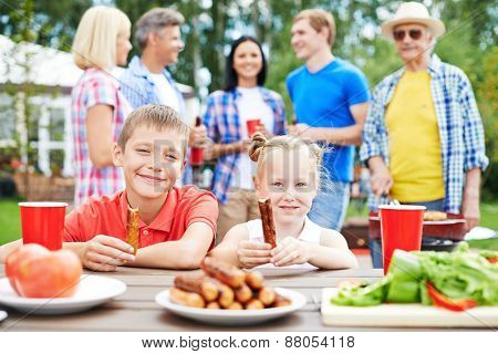 Cute siblings with sausages eating outdoors with their parents on background