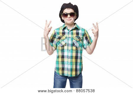 Little Boy With A Cap And Glasses Doing Victory Gesture. Isolated On White Background