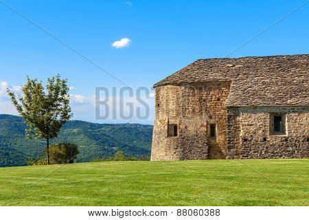 Lone tree and old stone church on green lawn under blue sky in Piedmont, Northern Italy.