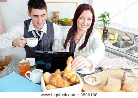 Couple Of Businesspeople Using A Laptop During Their Breakfast