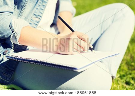 lifestyle, summer vacation, education and people concept - close up ofyoung girl writing with pencil to notebook and sitting on grass in park