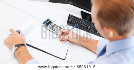 business, office, school and education concept - businessman with notebook and calculator