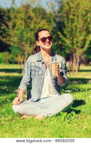 lifestyle, summer vacation, drinks and people concept - smiling young girl drinking coffee from paper cup and sitting on grass in park