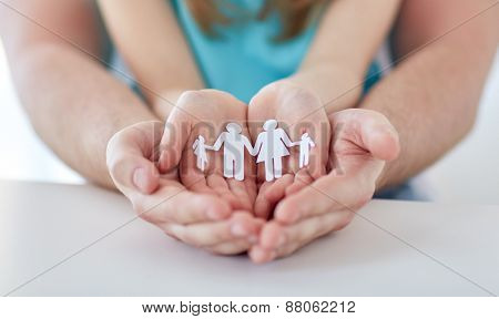 people, charity and happiness concept - close up of father and girl holding paper family cutout in cupped hands at home
