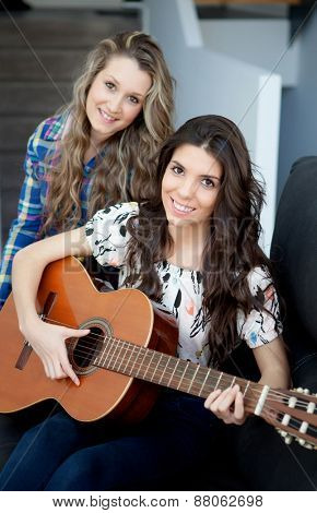Two pretty girls playing guitar at home