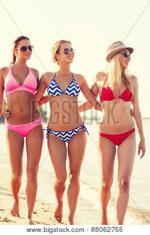 summer vacation, holidays, travel and people concept - group of smiling young women on beach