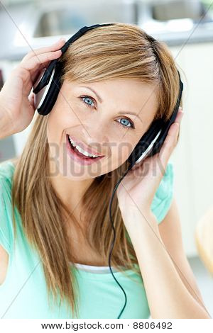 Delighted Caucasian Woman Listening To Music With Headphones In The Kitchen