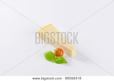 slice of parmesan cheese, cherry tomato an basil on white background