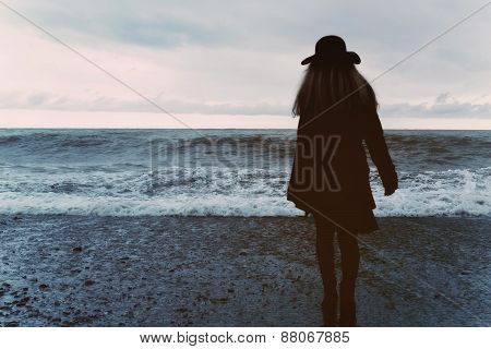 Woman In A Black Coat On The Beach