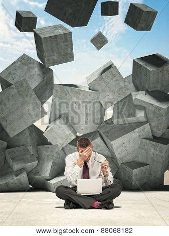 sit businessman and falling concrete cubes