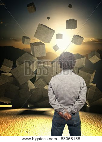 man look croncrete abstract cubes falling from the sky