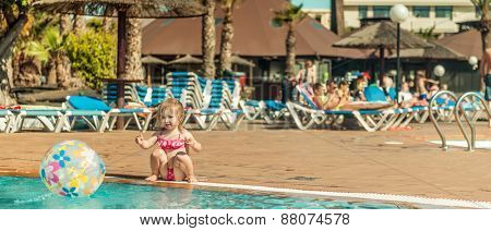 little cute girl sitting near the pool with a ball. panoramic framing