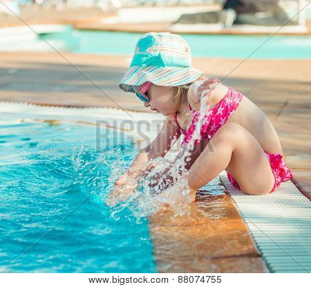 little cute girl sitting near the pool with a circle for swimming