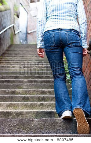 Young Woman In Jeans Going Up Stip Stairs