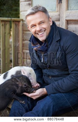 Mature Man Feeding Pet Micro Pig