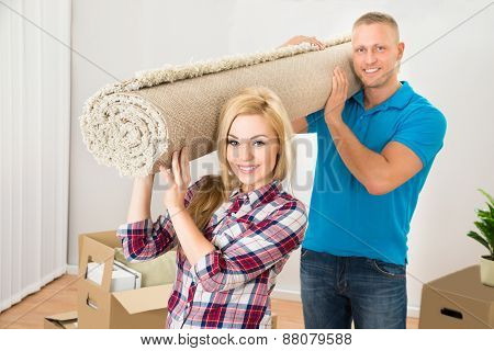 Couple Carrying Rolled Carpet