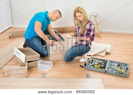 Couple Assembling Wooden Drawers
