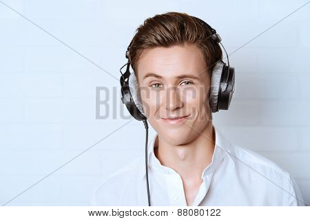 Smiling young man in white shirt listening to music in headphones.