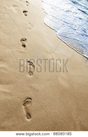 Footsteps in the sand on the beach
