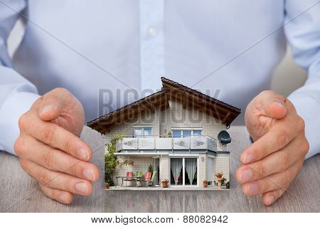 Close-up Of Man Saving Small House Model