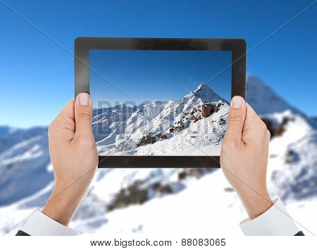 Close-up Of Person Hand Taking Photo Of Snowy Mountain