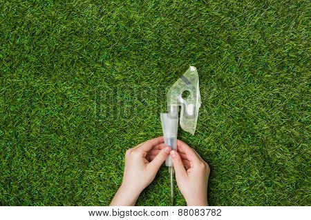 Hands holding inhaler mask over green grass.
