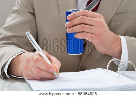 Businessman With Drink Can And Document