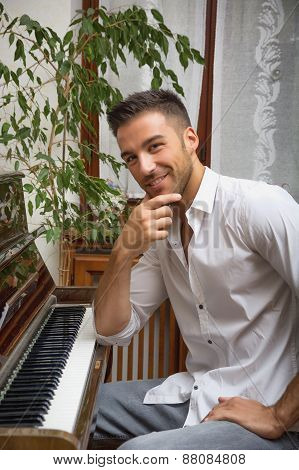 Young handsome male artist sitting at wooden classical upright piano