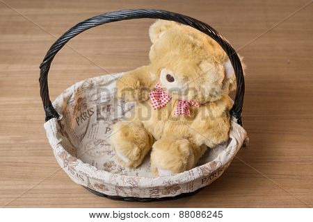 Toy Teddy Bear In Basket Isolated On Wooden Desk
