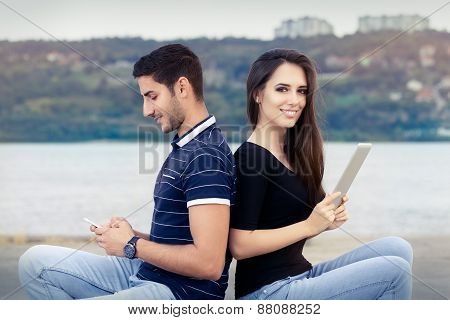 Happy Couple Checking their Smartphone and Tablet