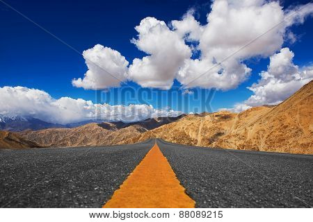 Long road in desert and blue sky background.