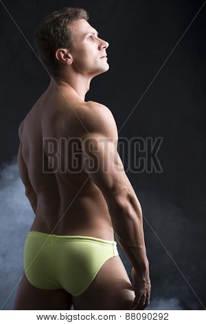 Handsome shirtless muscular man's back, looking up to a side