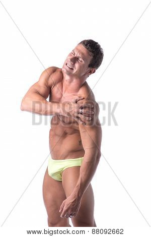 Muscular handsome man holding his shoulder in pain