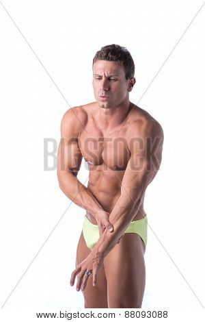 Muscular handsome man holding his arm in pain