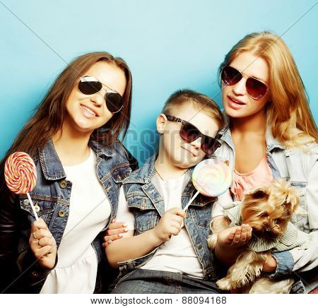 happy two sisters and brother with yorkshire terrier