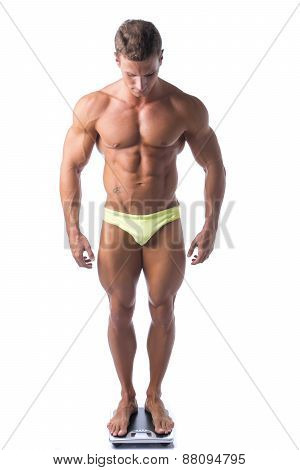 Muscular young man weighing himself on scale, isolated