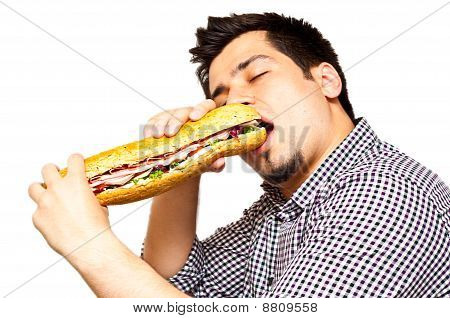 Young Man Eating A Freshly Made Sub Meat Feast Sandwich