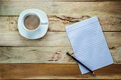 picture of hot coffee  - Top view shot Paper and pencil with hot coffee on wood table - JPG