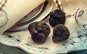 stock photo of truffle  - Three fresh mushrooms black truffle on a plate - JPG