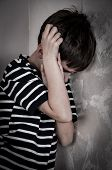 stock photo of scared  - Scared and abused young boy with hands on the head - JPG